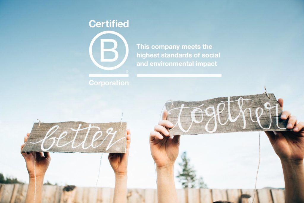 2 hands hold up signs that say better together. B Corporation Logo with text - this company meets the highest standards of social and environmental impact.